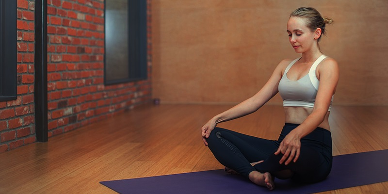 Vrouw op yogamat die reiki geeft tijdens yoga