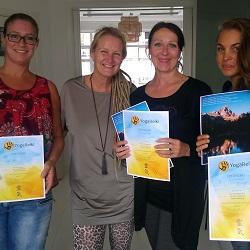 Drie vrouwen tonen elk een certificaat van YogaReiki-cursus